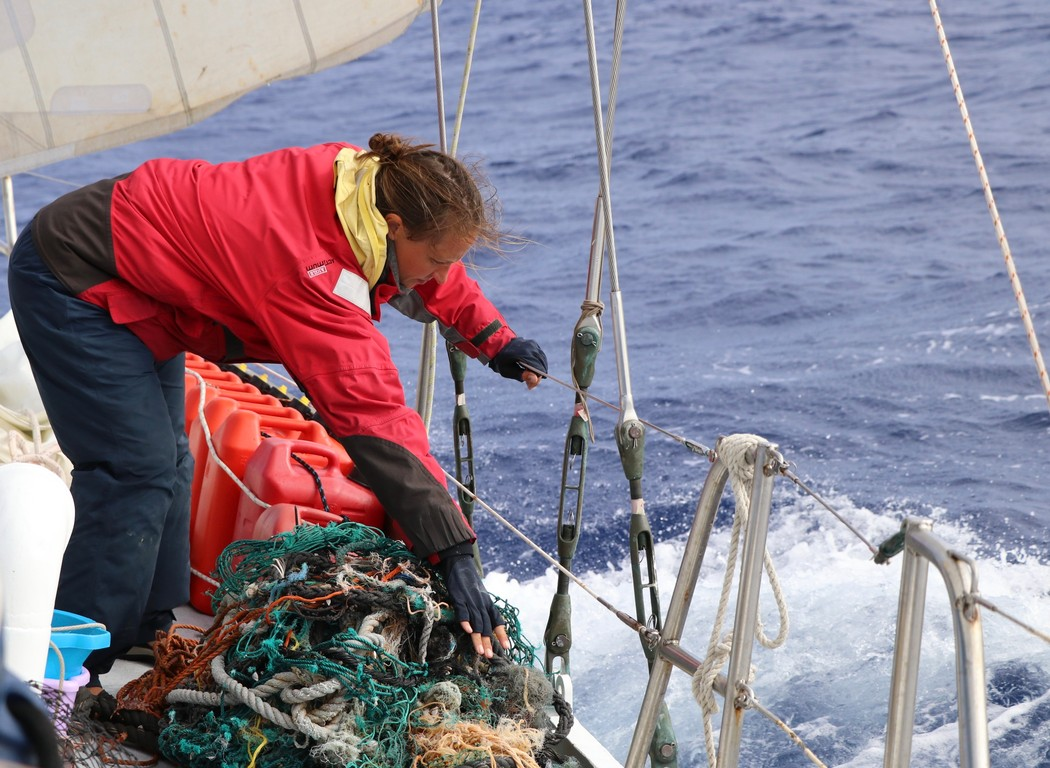 Plastic Change volunteer and scientist Malene Møhl helps secure a tangle of discarded fishing gear collected from the sea to the deck of S/Y Christianshavn. Image: Erica Cirino