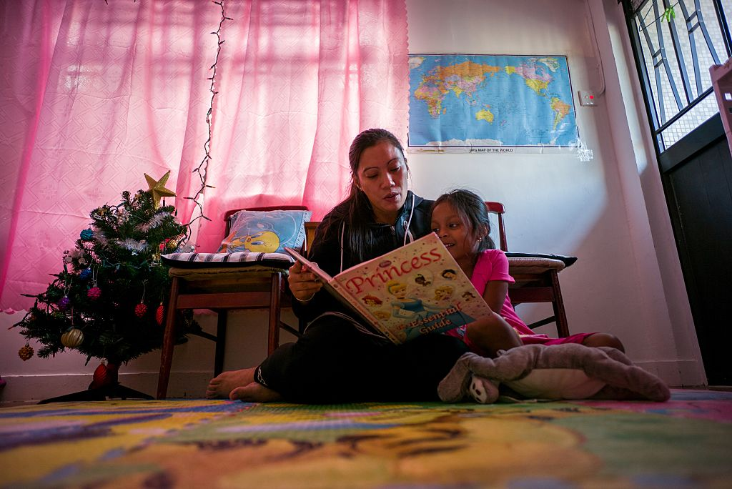 Filipino refugee Vanessa Rodel reads to her 4-year-old daughter.