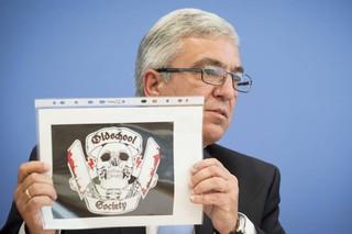 Roger Lewentz, Vorsitzende der Innenminister-Konferenz, zeigt auf einer Pressekonferenz das Logo der Oldschool Society.