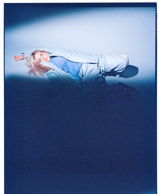 Billie Eilish lying on the floor in blue outfit