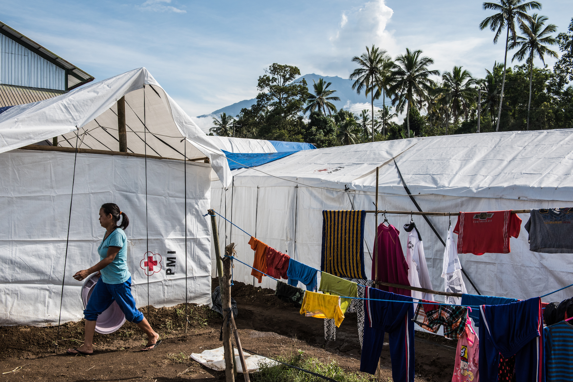 Mount Agung looms in the background as a woman walks past tents set up by the Indonesian Red Cross at an evacuation center in Rendang. & Evacuated Bali Residents Wonder If the Volcano Will Ever Stop ...