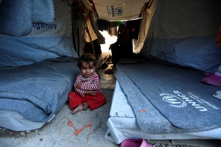 A one-year-old girl smiles as she sits with her mother at the Souda Refugee Camp in Chios island, Greece, June 10, 2017. (REUTERS/Zohra Bensemra)
