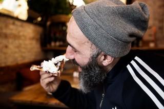 Ibrahim smager på pizzaen med flødeskum.
