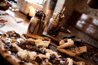 Et bord med varm kakao og dessertpizza.