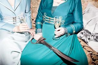 Henriette og Marianne i sofa med champagne i glasset og sabel på skødet.