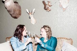 Henriette og Marianne skåler med champagneglas.