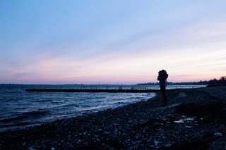 Sigrid står alene ved havet i solnedgangen.