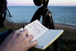 Sigrid Ilsøe skriver i en notesbog. Man kan se havet i baggrunden.
