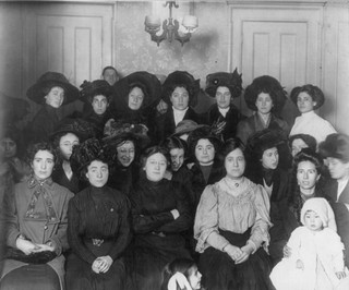 1520419180203-Group_of_mainly_female_shirtwaist_workers_on_strike_in_a_room_New_York