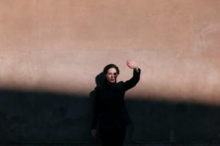 Leny står på af en mur og skygger for solen med sin ene hånd