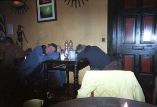 Drei Männer schlafen sich an einem Tisch ihren Rausch aus