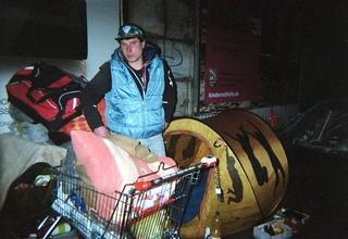 Ein junger Obdachloser zeigt seine Habseligkeiten zwischen Zelt und Einkaufswagen