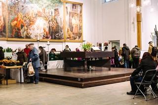 Mehrere alte Menschen stehen in einer Schlange rund um einen quadratischen Holzaltar und vor den Tischen mit dem Essen, darüber hängt ein großes Gemälde mit einer Picknickszene