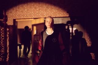 Lea står i projektørlys med boksehandsker på i en hal i Køge