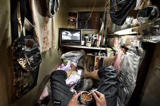 Ein Mann isst in einer der winzigen Wohnungen in Hongkong eine Dose Bohnen