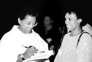 Die Dichterin Audre Lorde signiert auf der International Feminist Book Fair 1988 in Montreal ein Buch, neben ihr lächelt Katharina Oguntoye
