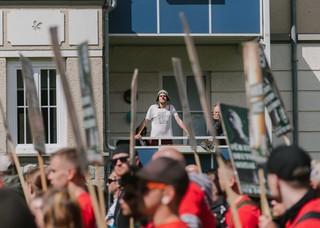 Junger Mann steht mit Clownsnase auf Balkon, im Vordergrund läuft die Demo des III. Wegs