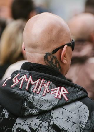 Ein Demoteilnehmer mit Glatze, Sonnenbrille, Faustring-Tattoo und Thor-Steinar-Pulli