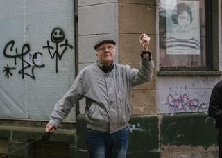 Älterer Herr in grauer Jacke und mit Hund hebt die linke Arm zur Faust
