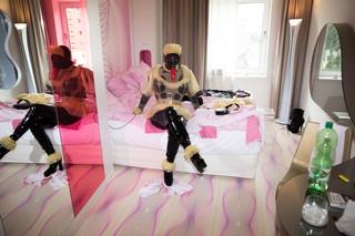 Die Gummipuppe sitzt auf ihrem Hotelbett, aus ihrem Gasmaskenmund hängt ein rotes Kondom
