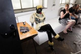 Die Gummipuppe sitzt auf einer Sofabank, beobachtet von einer eine Bockwurst verzehrenden Frau