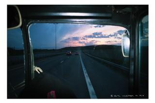 Der Bus rollt die Autobahn entlang, die Sonne geht auf