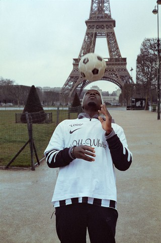 Model with football on their head by Eiffel Tower in Paris: Virgil Abloh for Nike