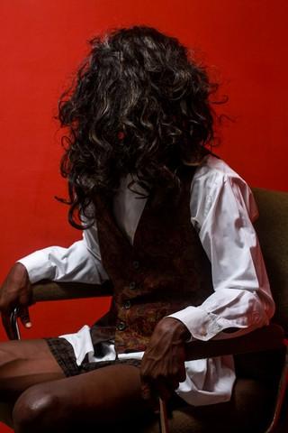 Ein Mensch sitzt in Langhaaarperücke kurzem Rock und Weste auf einem Bürostuhl, dass Gesicht verdeckt