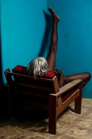 Ein Mensch sitzt in einem Sessel, den Rücken zum Betrachtenden gedreht, eine Perücke auf dem Kopf, das linke Bein hochgestreckt