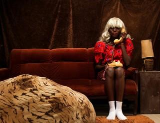 Ein Mensch in einem Kleid und unter einer Perücke telefoniert auf einem Sofa mit einem alten Wählscheiben-Telefon