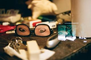 Eine Brille mit aufgeklebten Augen im Chaos