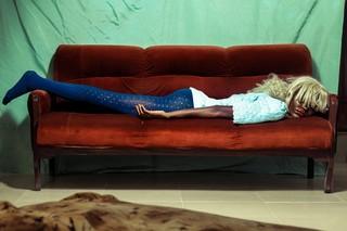 Ein Mensch in Strumpfhosen und mit Perücke liegt auf einer Couch, der Pony verdeckt die Augen