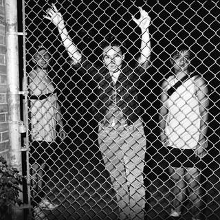 Eine junge Frau lehnt sich gegen den Zaun.