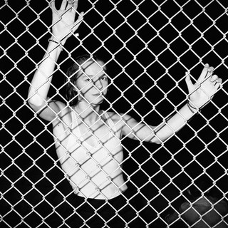 Eine Frau lehnt sich gegen den Zaun.