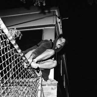 Ein junger Mann klettert über den Zaun zum Schwimmbad.