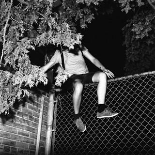 Ein Mann klettert über den Zaun zum Schwimmbad.