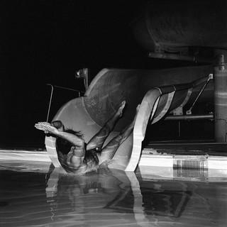 Ein Nackter rutscht mit viel Schwung ins Wasser.