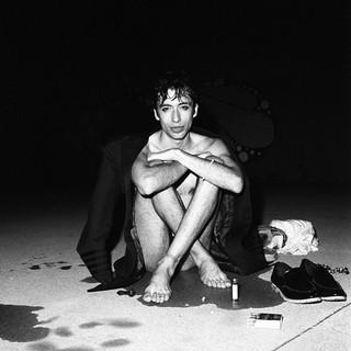 Ein junger Mann nach dem Schwimmen im Schneidersitz.