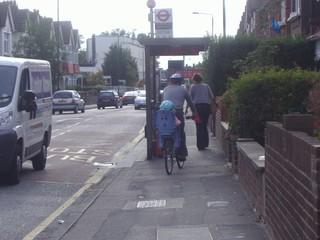 Ein Vater fährt mit Kind auf dem Fahrradsitz durch eine enge Bushaltestelle