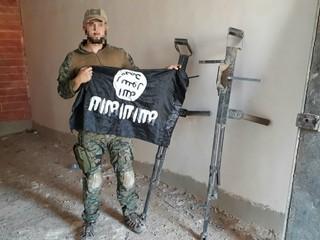Der deutsche Freiwillige YBS-Milizionär Martin Kamper mit IS-Flagge und Waffenattrappen.