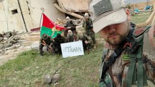 Der deutsche freiwillige YPS-Milizionär Martin Kamper posiert Kameraden mit YBS-Flagge und