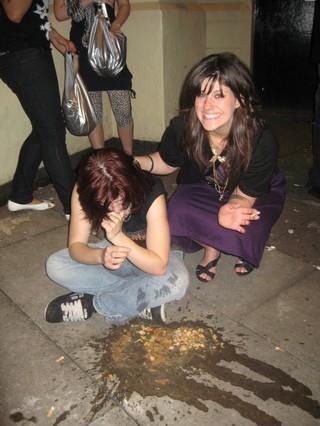Eine junge Frau kniet neben einer anderen Frau, die sich übergeben hat.