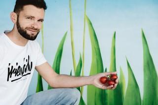 Growbox-Unternehmer Frost vor einer gemalten Wiese mit Tomaten in der Hand