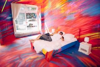 Ein Paar küsst sich auf einem Bett in einem bunt bemalten Raum