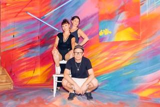 Drei Erwachsene in szenigen Klamotten hocken vor einer bunten Wand