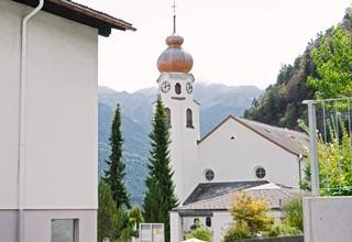 Eine Kirche hebt sich von einem Bergpanorama ab