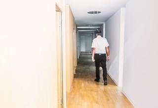 Ein älterer Mann schreitet einen Büroflur entlang