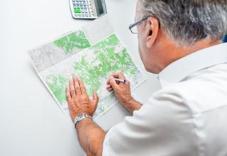 Der Bürgermeister markiert einen Punkt auf einer Landkarte des Dorfes
