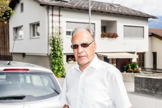 Der Bürgermeister trägt eine Sonnenbrille und steht vor einem Wohnhaus