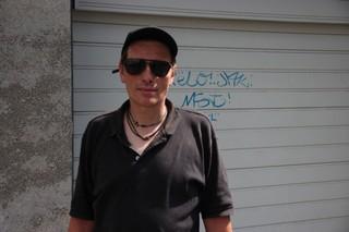 Ein Mann mit Sonnenbrille und offenem Hemd steht vor einer Einfahrt